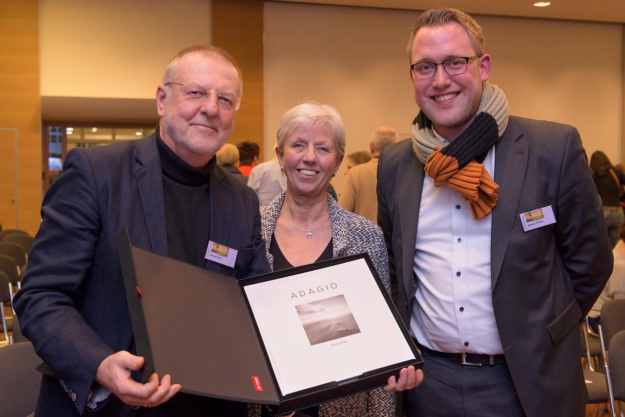 Bastian Freese von der Firma CEWE überreichte Bernd Walz und seiner Frau Gundula ein zur Ausstellung produziertes Fotobuch.
